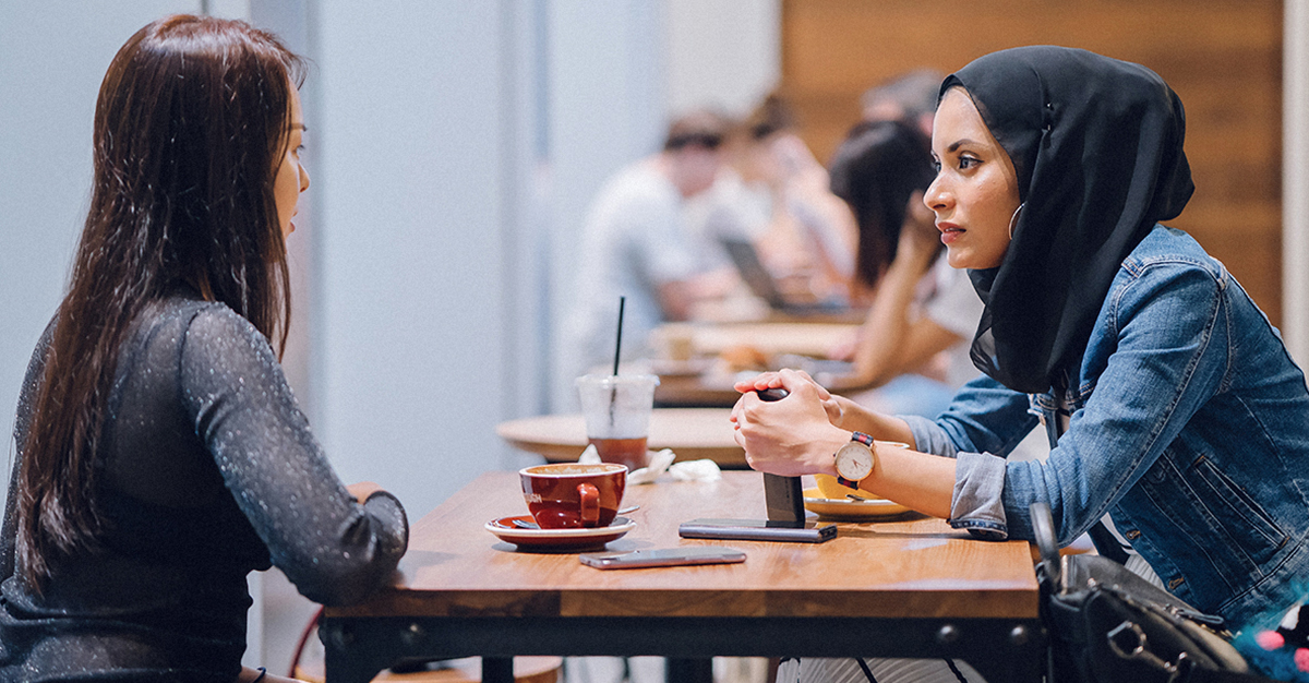 Two friends talk over coffee.