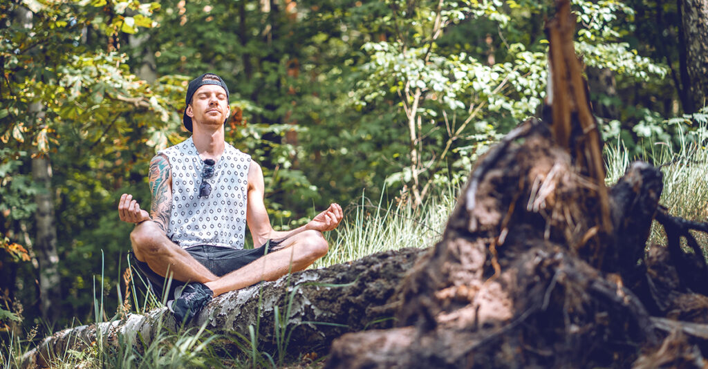 A man meditates in the forest.