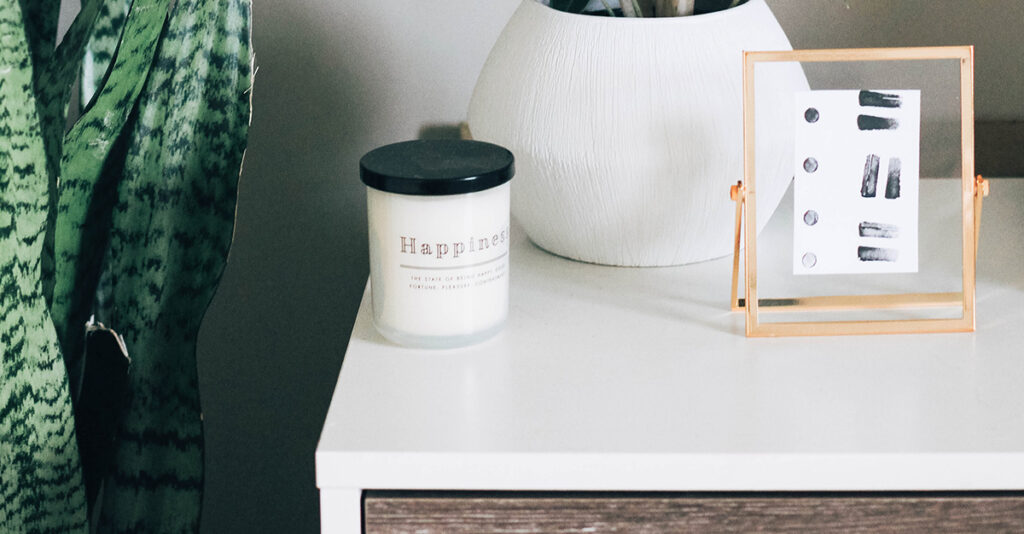 Candle and plant on nightstand